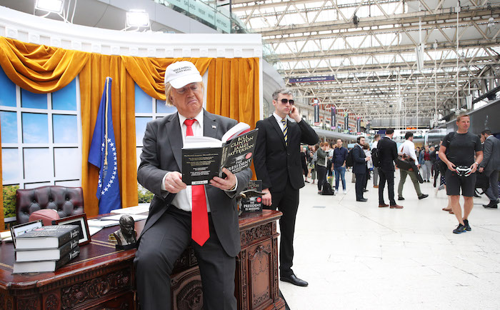 "FREE FOR EDITORIAL USE - A 'President Trump' lookalike brings The Oval Office to London's Waterloo Station to mark today's global release of James Patterson and Bill Clinton's co-authored thriller, ""The President Is Missing""."