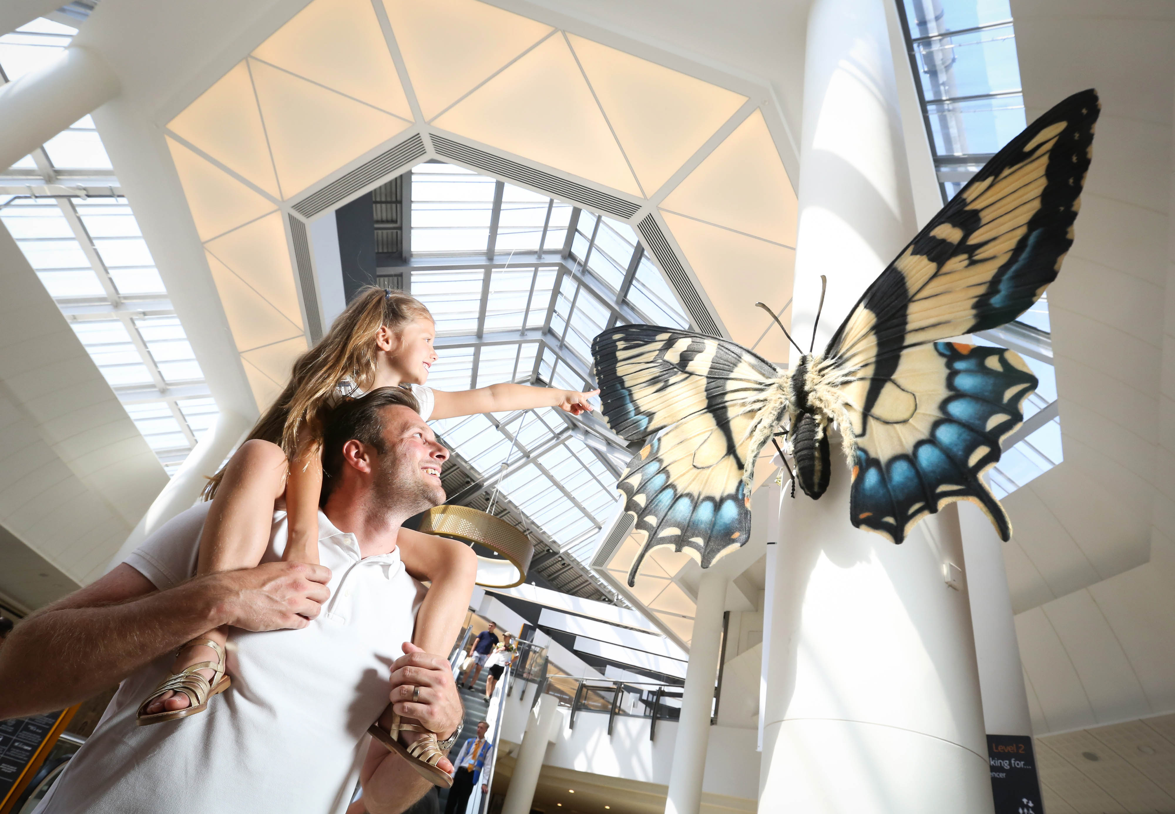 EDITORIAL USE ONLY Lee Riddell and his daughter Eva, aged 6, interact with a 9ft wide lifelike model of a Swallowtail Butterfly at the launch of Big Bugs on Tour at intu Lakeside, which is a year-long initiative designed to reconnect people with nature. The bugs have been created following research that found being closer to nature makes you 67 per cent happier, yet one in six children haven't seen a single bug in six months, one in ten kids don't know honey came from bees, and one in four parents can't tell the difference between a bee and a wasp. The tour will be visiting 13 intu centres nationwide over the next year. Photo credit should read: Matt Alexander/intu